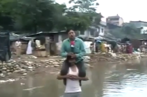 Indian-TV-reporter-Narayan-Pargaien-files-report-on-flood-from-victims-shoulders